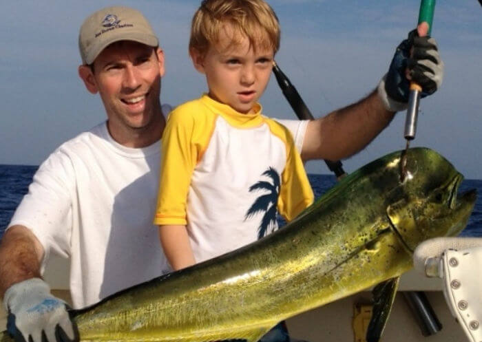 Mate and young angler holding out a big Cape Hatteras mahi.